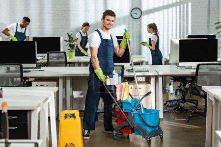 Foto de Carro de mudanza limpiador alegre con artículos de limpieza cerca de colegas multiculturales - Imagen libre de derechos