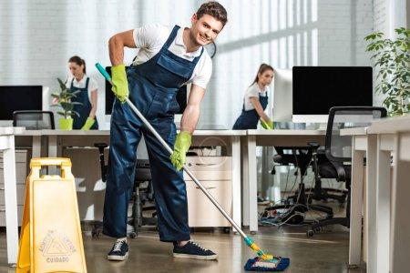 Photo pour Un jeune nettoyeur regardant la caméra en lavant le plancher avec la vadrouille dans un bureau moderne - image libre de droit