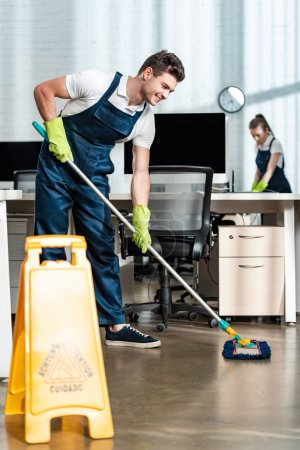 Photo for Smiling cleaner washing floor with mop near colleague cleaning desk - Royalty Free Image