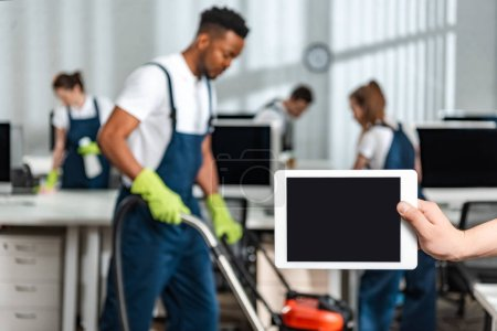 Photo pour Picture of man holding digital tablet with blank screen near team of multicultural cleaners - image libre de droit