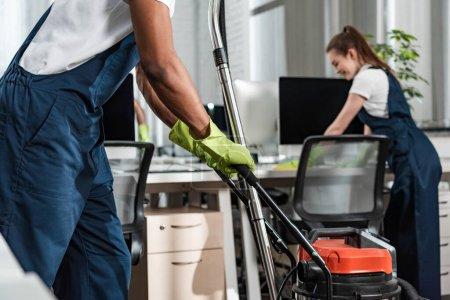 Foto de Vistas rotas de limpiador africano-americano moviendo aspirador en el despacho. - Imagen libre de derechos