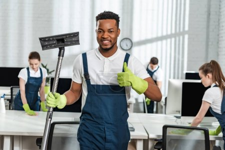 Photo pour Nettoyant afro-américain souriant tenant brosse aspirateur et montrant pouce vers le haut près de l'équipe de collègues - image libre de droit