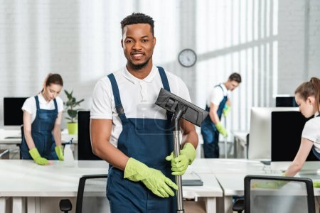 Photo for Smiling african american cleaner holding vacuum cleaner brush near team of multicultural colleagues - Royalty Free Image