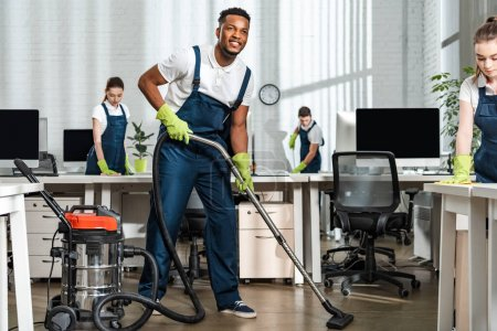 Photo for Smiling african american cleaner vacuuming floor near team of multicultural colleagues - Royalty Free Image