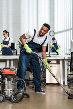 Photo pour Souriant afro-américain nettoyant aspirateur plancher tout en regardant loin - image libre de droit