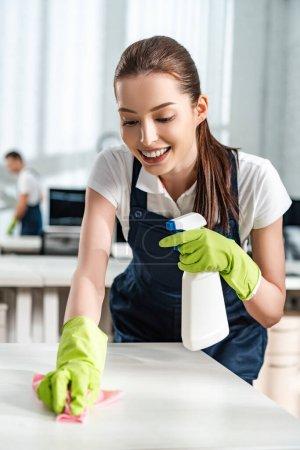 glücklich Reiniger hält Sprühflasche während Waschtisch mit Lappen