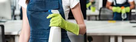 Photo for Cropped view of young cleaner in overalls holding spray bottle with detergent - Royalty Free Image