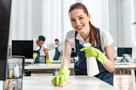 Photo for Selective focus of smiling cleaner washing office desk with rag - Royalty Free Image
