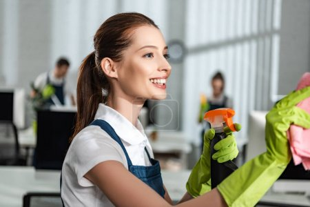 happy, attractive cleaner holding detergent spray and rag while cleaning office