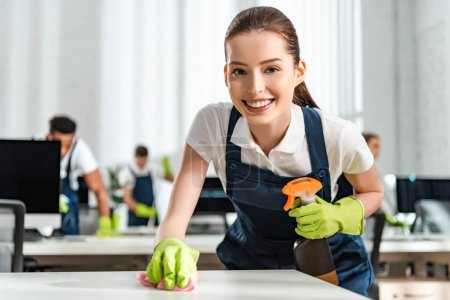 Photo for Happy cleaner looking at camera while cleaning office desk with rag - Royalty Free Image