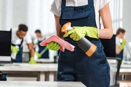 Photo for Cropped view of cleaner in uniform spraying detergent on rag - Royalty Free Image