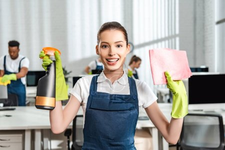 Photo for Happy cleaner in overalls holding spray bottle and rag while looking at camera - Royalty Free Image