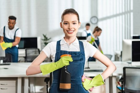 Photo for Happy cleaner standing with hand on hip and holding spray bottle while looking at camera - Royalty Free Image