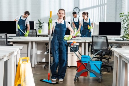 Photo pour Attrayant nettoyant tenant la serpillière debout avec la main sur la hanche près de collègues multiculturels - image libre de droit
