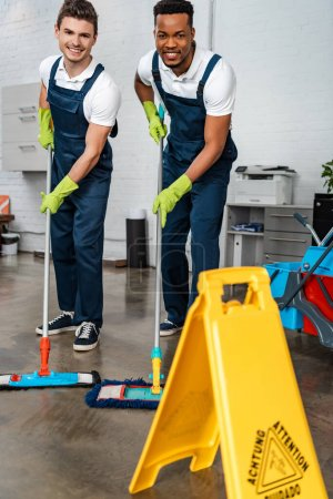 Photo for Smiling multicultural cleaners washing floor with mops near wet floor caution sign - Royalty Free Image