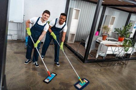 Photo pour Deux nettoyeurs multiculturels souriants laver le sol avec des vadrouilles et regarder la caméra - image libre de droit