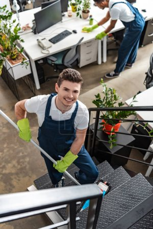 high angle view of young cleaner washing cleaning stairs with mop