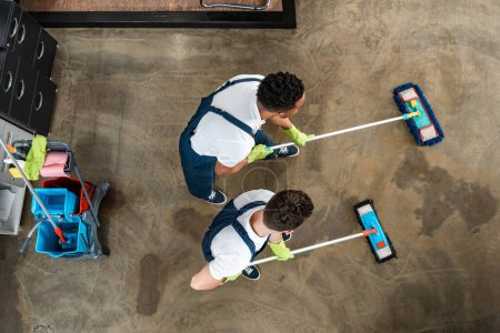 Photo for Top view of two multicultural cleaners washing floor with mops - Royalty Free Image