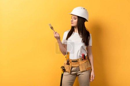 Photo pour Sérieux bricoleur tenant et regardant pinceau de peinture sur fond jaune - image libre de droit