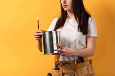 Photo pour Vue recadrée de bricoleuse tenant la boîte de peinture et le pinceau sur fond jaune - image libre de droit