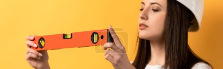 Photo for Panoramic shot of concentrated handywoman holding spirit level on yellow background - Royalty Free Image