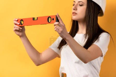 Photo for Cropped view of concentrated handywoman holding spirit level on yellow background - Royalty Free Image