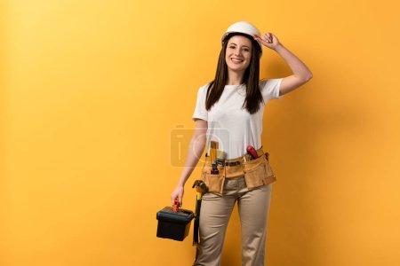 Photo pour Souriant bricoleur dans casque tenant boîte à outils sur fond jaune - image libre de droit