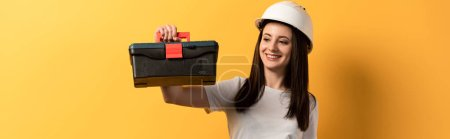 Photo for Panoramic shot of smiling handywoman in helmet holding toolbox on yellow background - Royalty Free Image