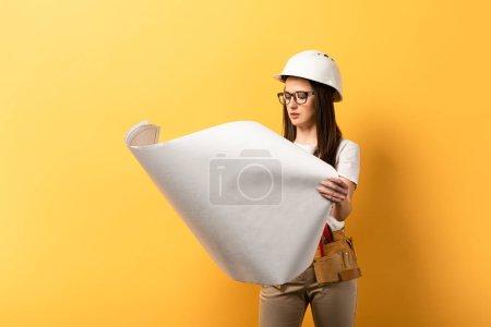Photo pour Attrayant bricoleur dans casque regardant le plan sur fond jaune - image libre de droit