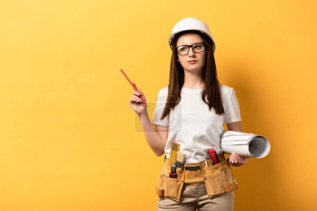 Photo for Thoughtful handywoman holding blueprint and pencil on yellow background - Royalty Free Image