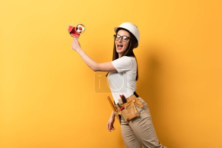 Photo for Shocked handywoman holding tape dispenser on yellow background with copy space - Royalty Free Image