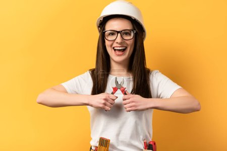 Photo for Smiling handywoman holding pliers and looking at camera on yellow background - Royalty Free Image