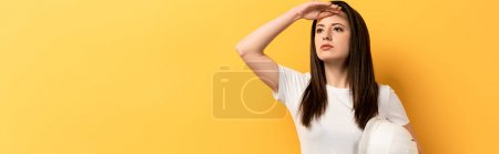 Photo for Panoramic shot of serious handywoman holding helmet and looking away on yellow background - Royalty Free Image