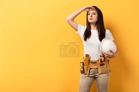Photo pour Grave bricoleuse tenant casque et regardant loin sur fond jaune - image libre de droit