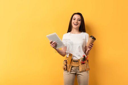 Photo for Smiling handywoman holding paper cup and digital tablet on yellow background - Royalty Free Image