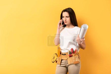 Photo pour Sérieux bricoleuse parler sur smartphone et projet de tenue sur fond jaune - image libre de droit