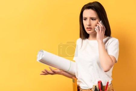 Foto de Shock handywoman hablando por teléfono inteligente y sosteniendo el proyecto en el fondo amarillo. - Imagen libre de derechos