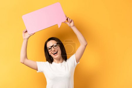 smiling woman holding speech bubble with copy space on yellow background