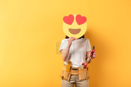 Photo for KYIV, UKRAINE - DECEMBER 16, 2019: repairwoman obscuring face with smiley with heart eyes and holding pliers on yellow background - Royalty Free Image