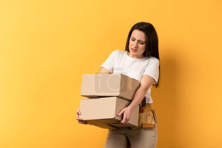 Photo for Tired repairwoman holding carton boxes on yellow background - Royalty Free Image