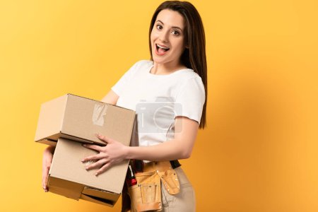 Photo for Shocked repairwoman  holding cardboard boxes on yellow background - Royalty Free Image