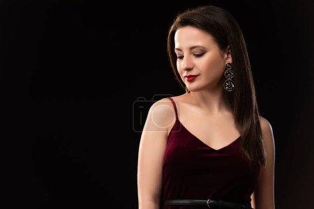Photo pour Jolie femme en robe regardant vers le bas isolé sur noir - image libre de droit