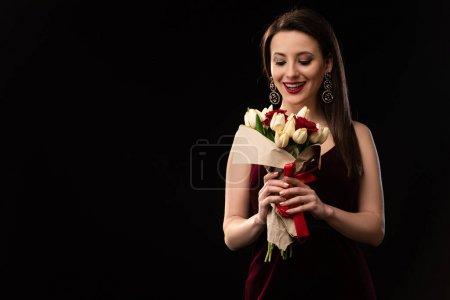 Photo pour Femme excitée en robe regardant le bouquet isolé sur le noir - image libre de droit