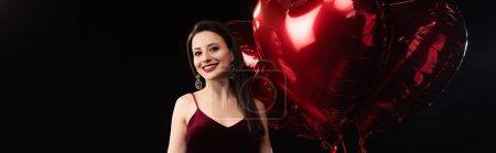 Photo pour Plan panoramique de femme souriante en robe tenant des ballons en forme de coeur en 14 février isolé sur noir - image libre de droit