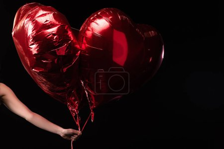Photo pour Vue en coupe d'une femme tenant des ballons en forme de coeur en 14 février isolée sur noir - image libre de droit
