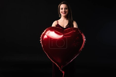 Photo for Smiling woman holding heart-shaped balloon in 14 february isolated on black - Royalty Free Image