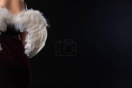Photo pour Vue recadrée de la femme en robe avec des ailes isolées sur noir - image libre de droit