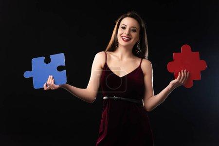 Photo pour Femme souriante en robe tenant des figures de puzzle isolé sur noir - image libre de droit