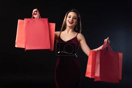 Photo pour Une femme souriante en robe tenant des sacs à provisions sur fond noir - image libre de droit