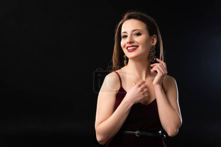 Photo for Smiling woman in dress with earrings looking at camera on black background - Royalty Free Image